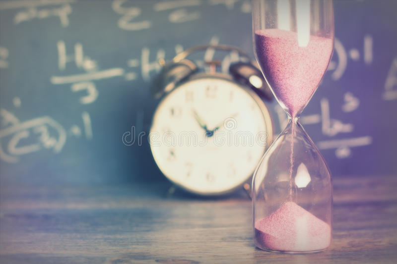 Hourglass on wood with a blackboard background. Hourglass against on wooden surface with a blackboard background stock photo