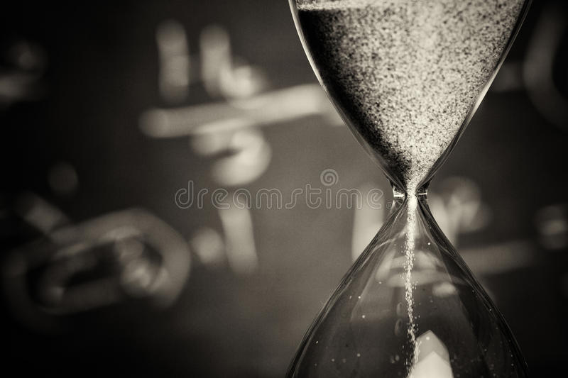 Hourglass on wood with a blackboard background. Hourglass against on wooden surface with a blackboard background royalty free stock photography
