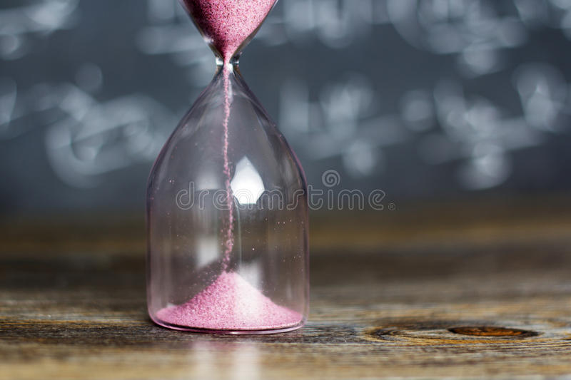 Hourglass on wood with a blackboard background. Hourglass against on wooden surface with a blackboard background stock images