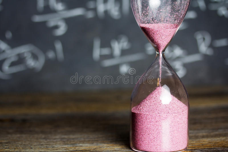 Hourglass on wood with a blackboard background. Hourglass against on wooden surface with a blackboard background royalty free stock images