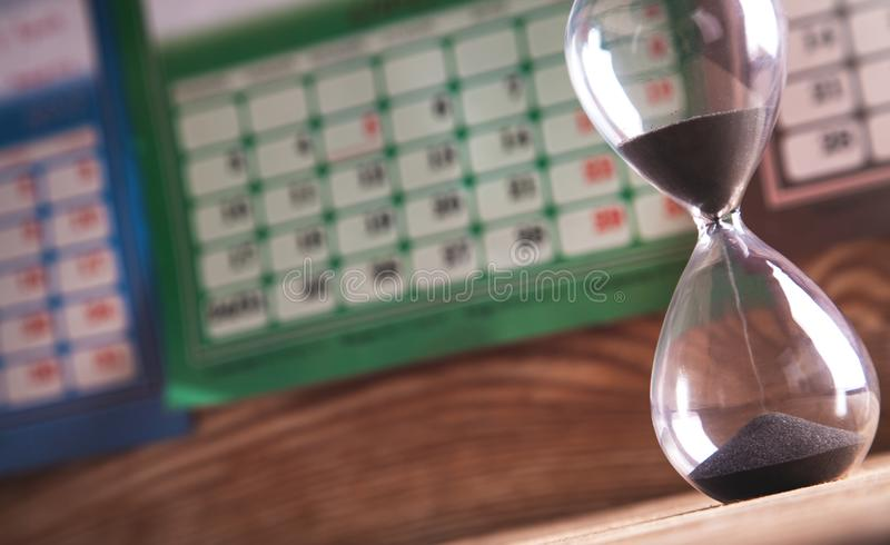 Hourglass on the wooden table in calendar background. Deadline concept stock photo
