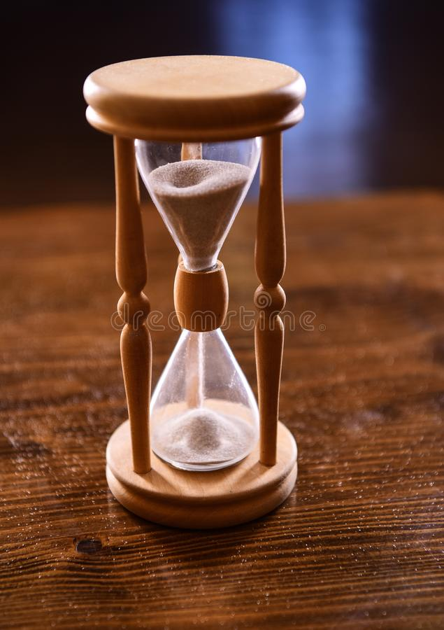 Hourglass on wooden table, dark background. Sand falling down inside of hourglass. Time flow concept. Wooden hourglass. Hourglass on wooden table, dark royalty free stock photography