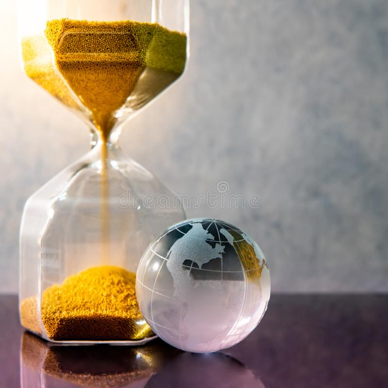 Hourglass and world globe crystal on the table royalty free stock photos