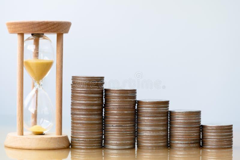 Hourglass złocisty piasek i sterta monety obrazy stock