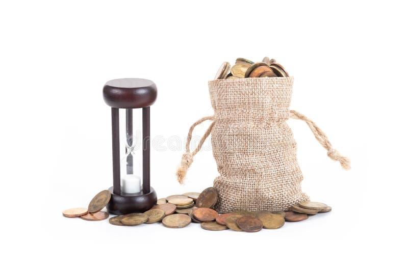 Hourglass z pieniądze zdojest i monety na białym tle Czas inwestować, czas wartość dla pieniądze, planowanie rodziny, pieniądze o obrazy royalty free
