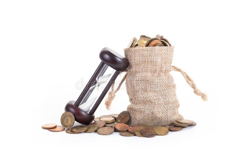 Hourglass z pieniądze zdojest i monety na białym tle Czas inwestować, czas wartość dla pieniądze, planowanie rodziny, pieniądze o zdjęcia royalty free