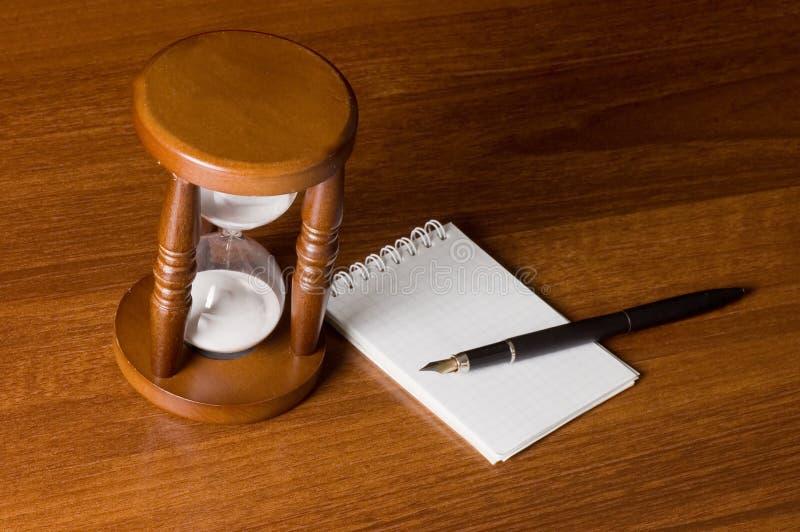 Hourglasses e caderno fotografia de stock royalty free