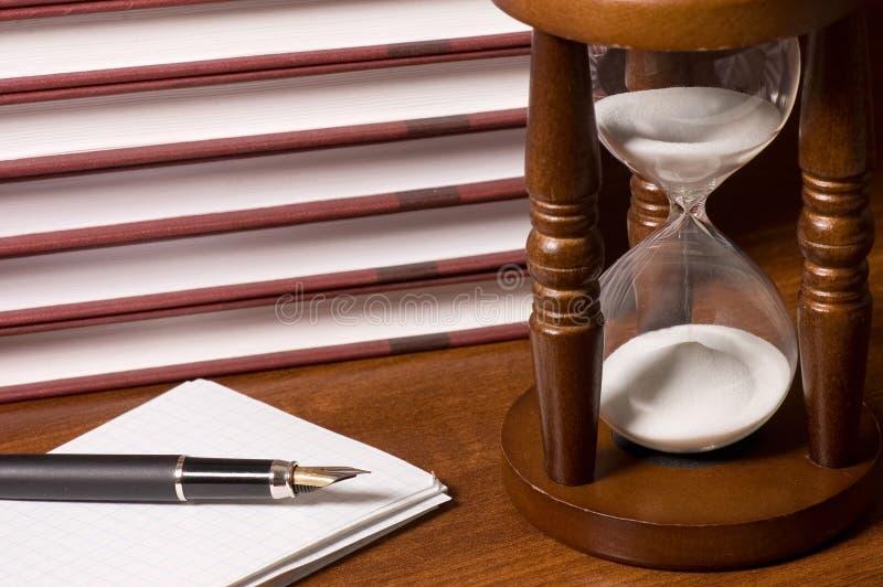 Hourglasses e livro em uma tabela de madeira fotos de stock