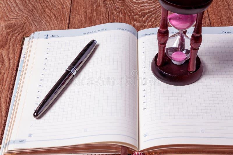 Hourglasses e livro em uma tabela de madeira foto de stock