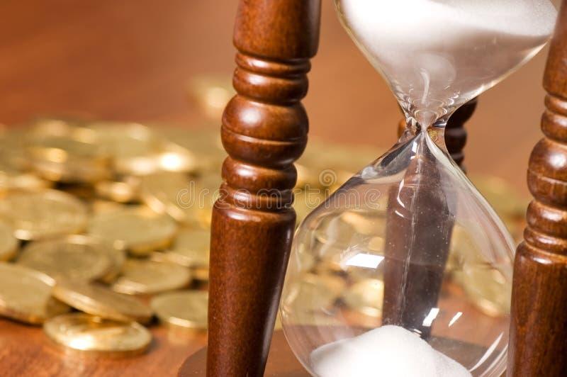 Hourglasses e moeda em uma tabela de madeira imagens de stock