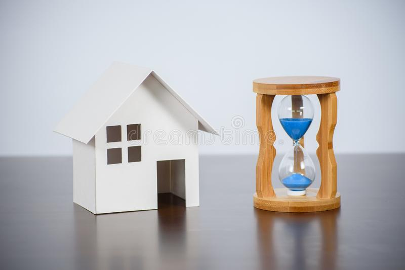Hourglasses with model house on a wooden table. stock photo