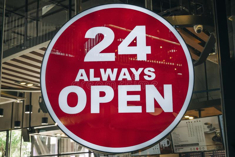 24 Hours Always Open Sign in front of the regular coffee cafe or co-working space in the city new trend of working space.  royalty free stock photo