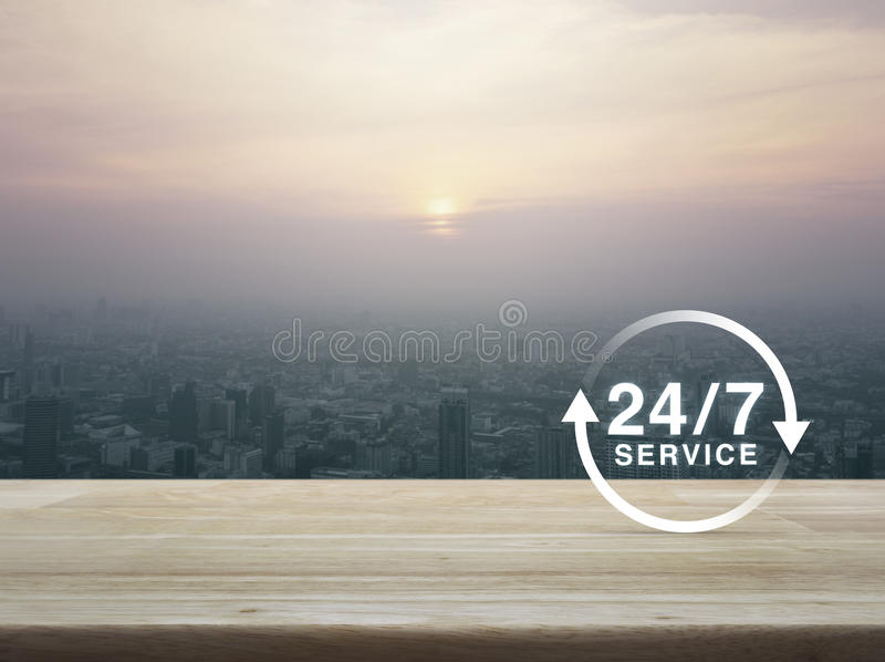 24 hours service icon on wooden table over aerial view of cityscape at sunset, vintage style, Full time service concept royalty free stock images