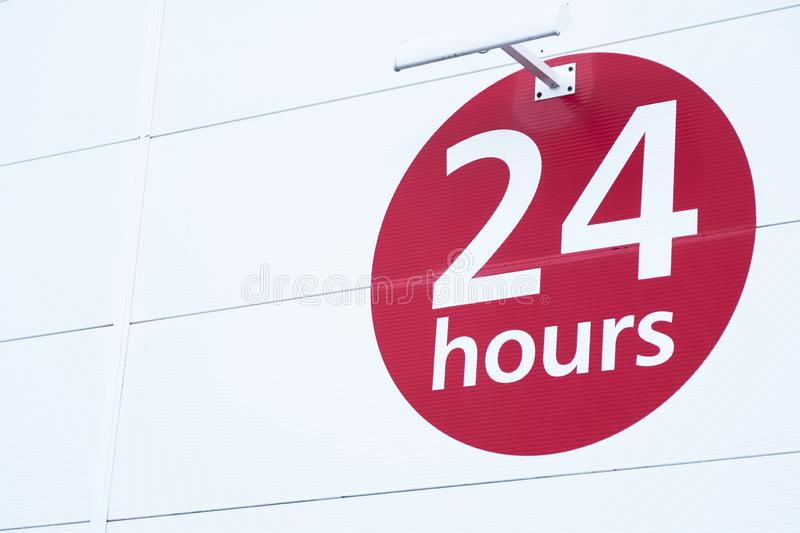 24 hours sign round red circle on white background for shop opening times. Uk royalty free stock photography