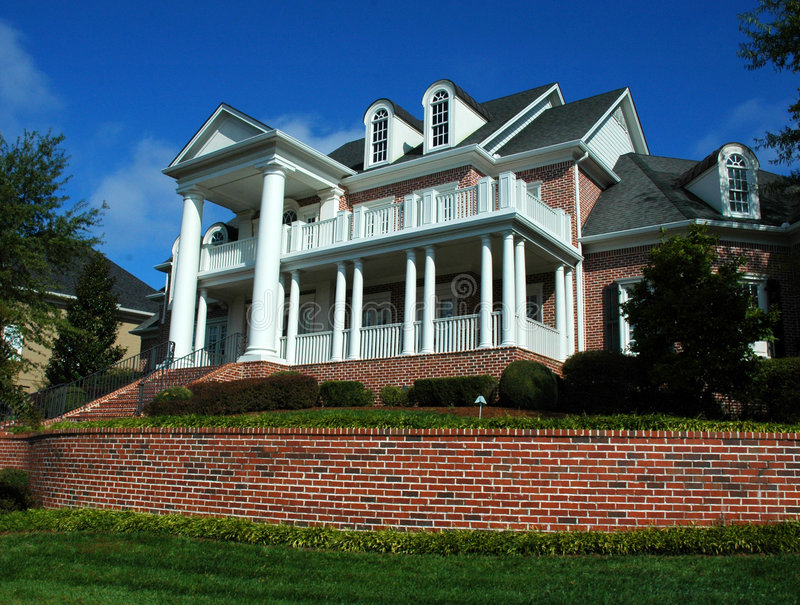 House. Large three-story house with a two-story porch several gables and an ornate columned entrance stock photography