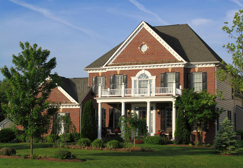 Two Story Brick House. Two story red brick house with white front balcony and flowerbed, Maryland, United States