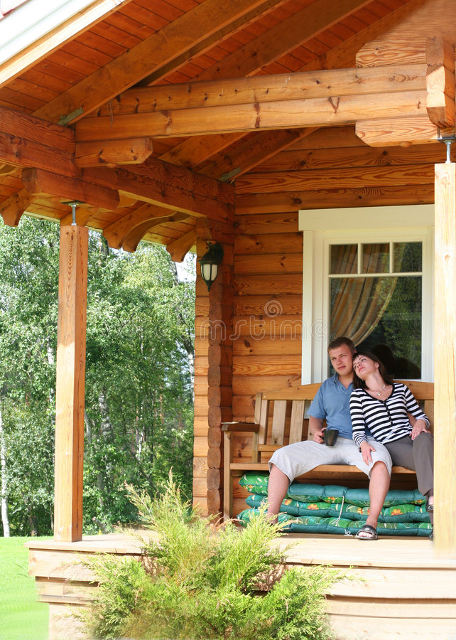 House. Young couple drinking tea on verandah royalty free stock images