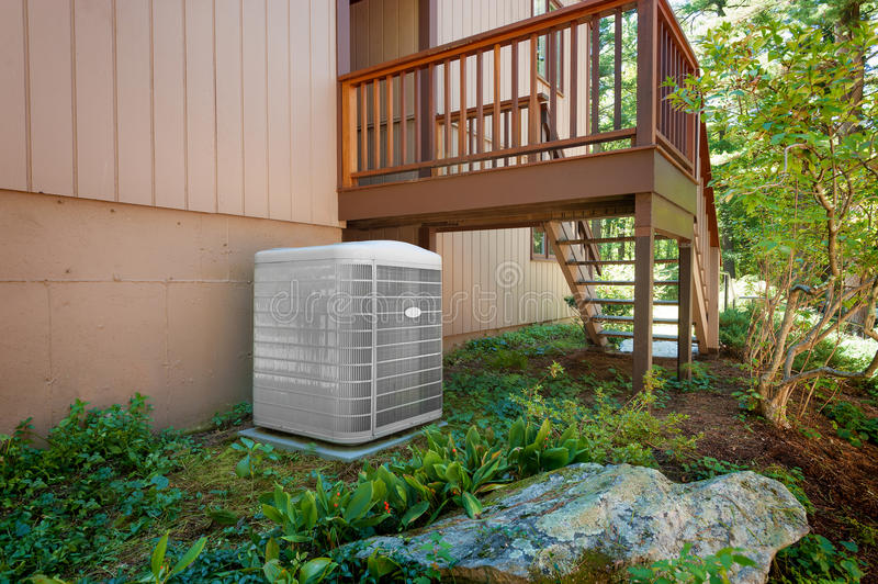 House air conditioning and heating unit. A residential central air conditioning and heating unit sitting outside a home royalty free stock photography