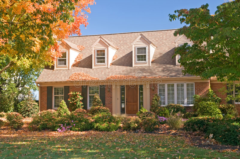 House in autumn. A view of a comfortable brick house with colorful autumn leaves on a bright fall day stock photos