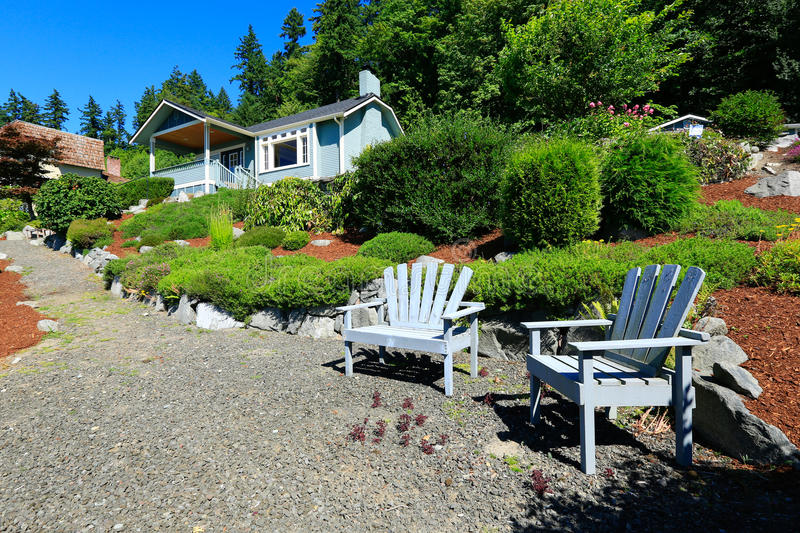 House with beautiful curb appeal and outdoor rest area. Port Orc. House with beautiful front yard landscape. and outdoor rest area with chairs. Port Orchard town royalty free stock photography