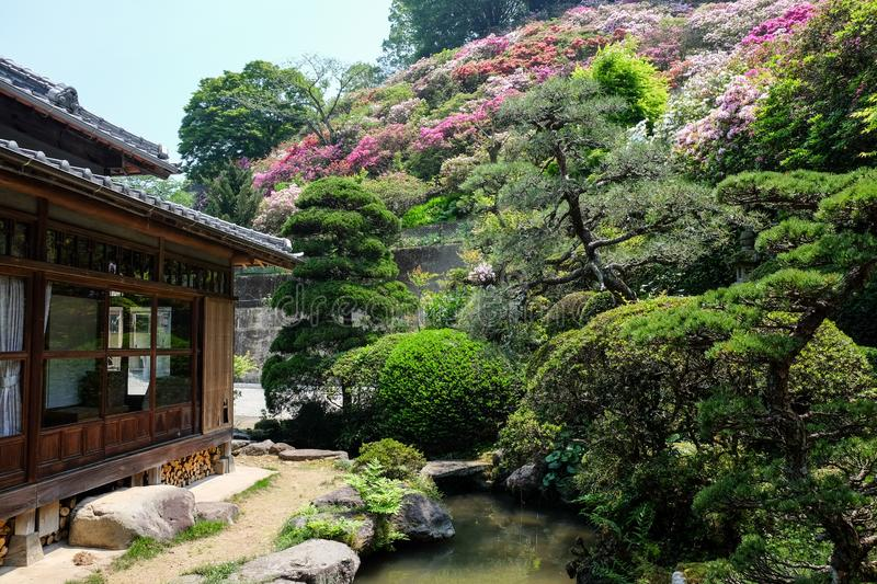 House, blooming flowers and river reflecting in onsen town, Yufuin, Oita, Kyushu stock photo