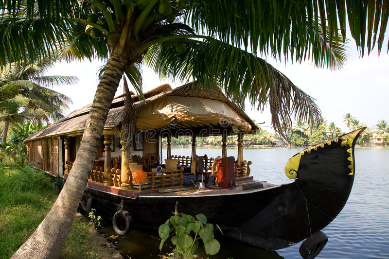 House boat in backwaters. House boat in India over tropical palm on the river stock image