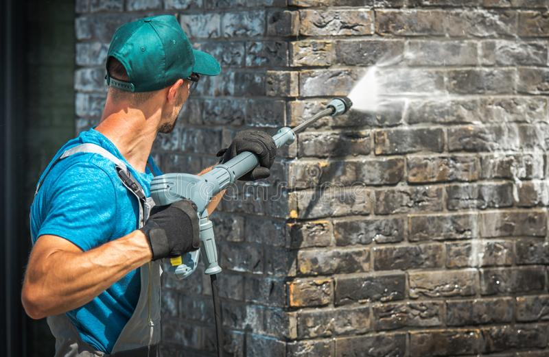 House Brick Wall Washing. Using Pressure Washer. Caucasian Worker in His 30s royalty free stock image