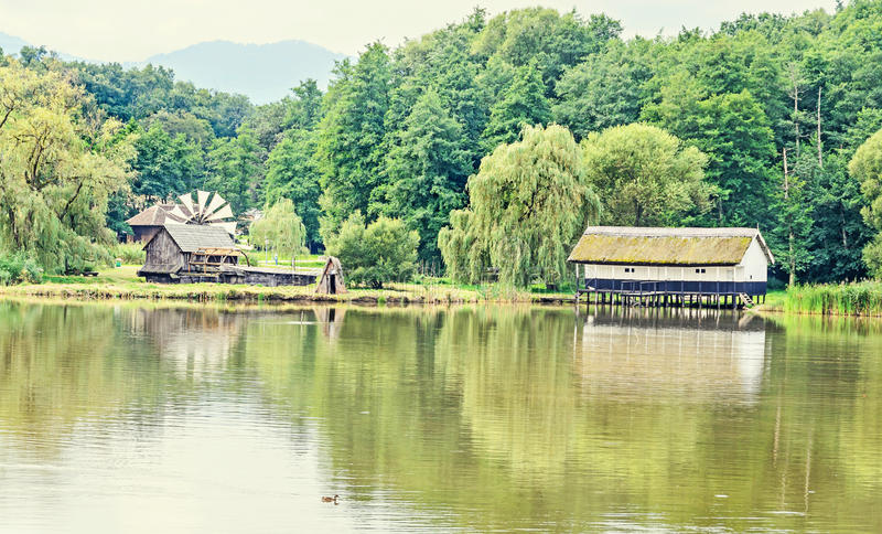 House build on water, straw roof, near lake and green forest royalty free stock photo