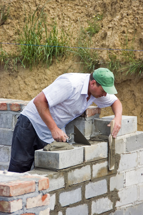 House builder at work. A house builder (bricklayer) at work. He is laying another block and checking if it's even stock image