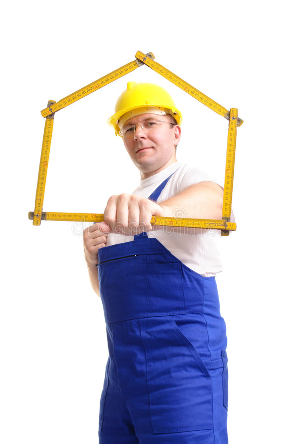 House building. Builder wearing blue jumpsuit and yellow helmet holding wooden ruler folded in house shape - over white background stock photos