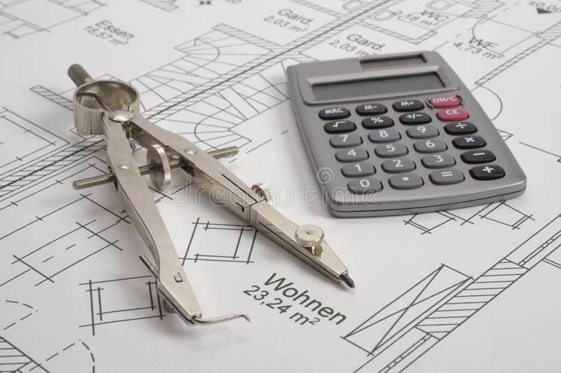 House building plan. An architectonic or construction plan for building a house, symbolic with hand calculator and compasses stock photography