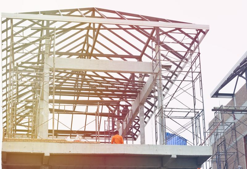 House building Saw the steel roof structure looking up to see the construction workers on the upper floor, stock images