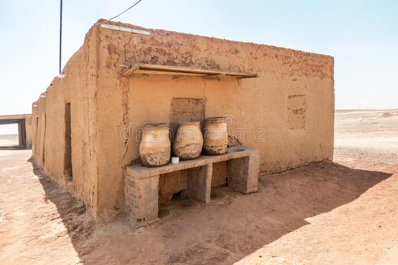 House built of mud bricks in the desert with a bench on which drinking clay jugs with water are standing ready. Sudan stock images
