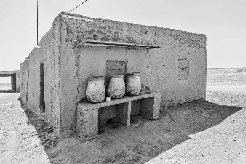 House built of mud bricks in the desert with a bench on which drinking clay jugs with water are standing ready, Sudan, black and. House built of mud bricks in royalty free stock photography