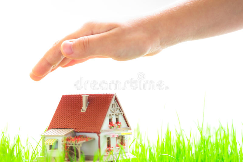 House in children`s hands. Children`s hands over model house. Real estate concept stock photo