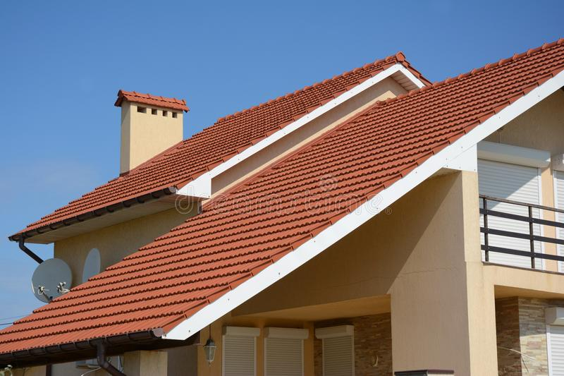 House with clay tile roof, rain gutter, chimney, gable and valley type of roof construction. Building attic house construction wit royalty free stock photography