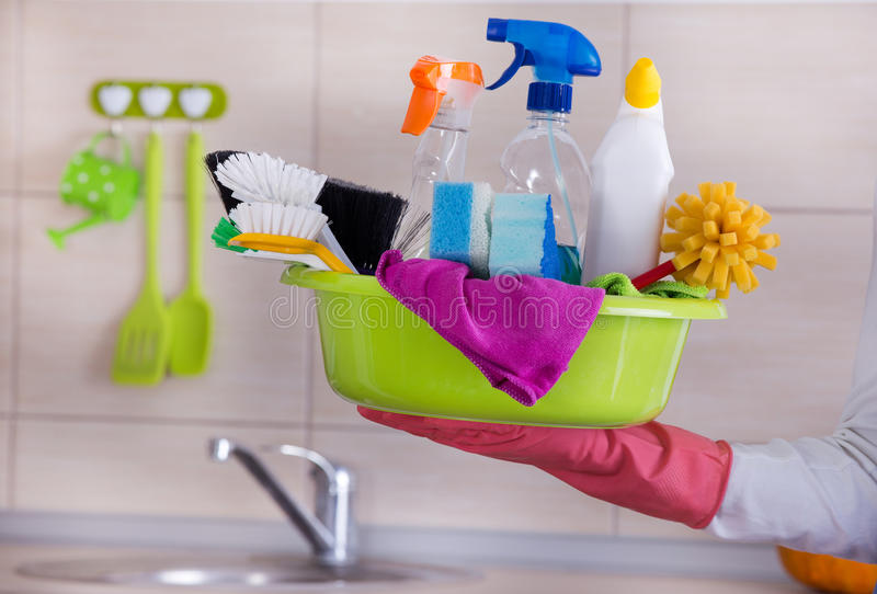 House cleaner carring cleaning supplies in one hand. Cleaning lady holding basin full of cleaning supplies in one hand in front of clean kitchen stock photo