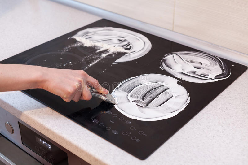 House cleaning. Housewife cleaning and polish electric cooker. Black shiny surface of kitchen top, hands with foam, glass scraper,. Bottle of cleaning agent stock image