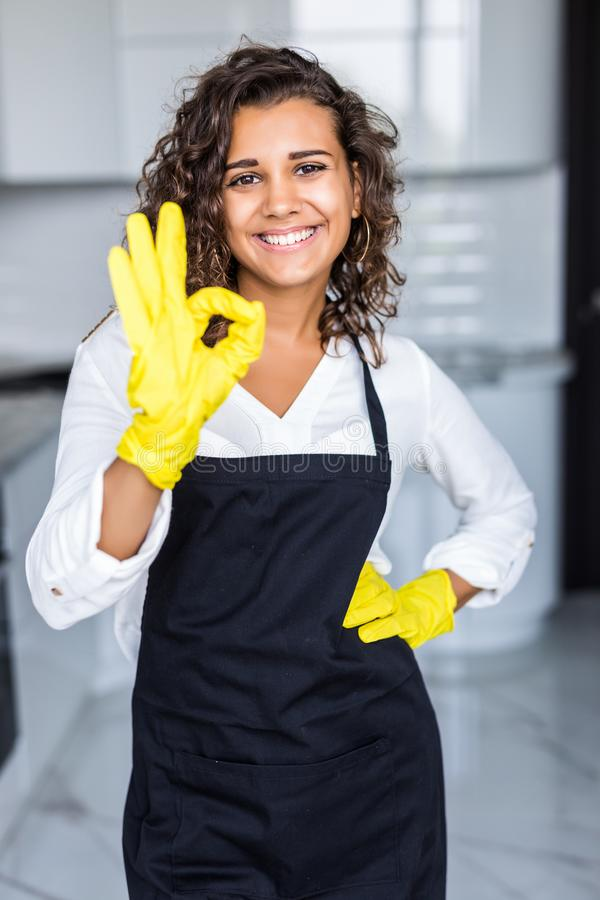 House cleaning service woman at kitchen. Latin american young woman with gloves, happy smile, okay sign pose royalty free stock images