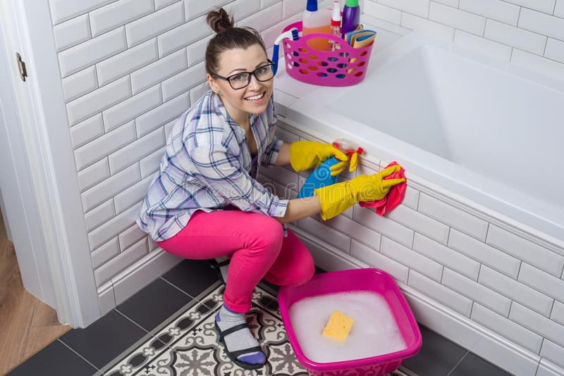 House cleaning. Woman is cleaning in the bathroom at home stock image