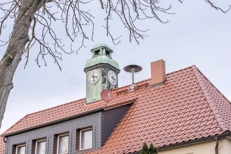 House with clock tower and siren of the local fire department on the roof. Excerpt of an exterior view of a building - seen from a public road - with a roof, on royalty free stock images