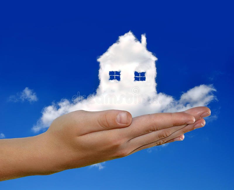 House from clouds. In the hand on blue sky royalty free stock photos