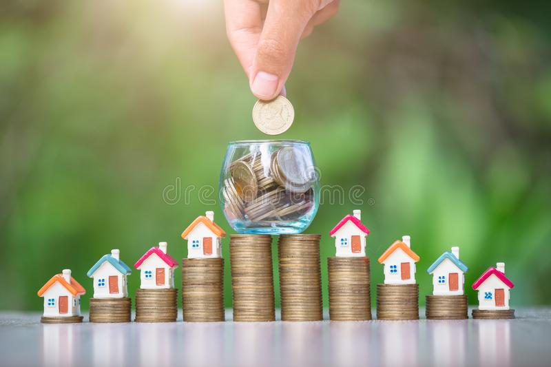 House on the coin ladder.In a glass jar have coins.The hand of a business person is going to place a coin.The concept of real stock image