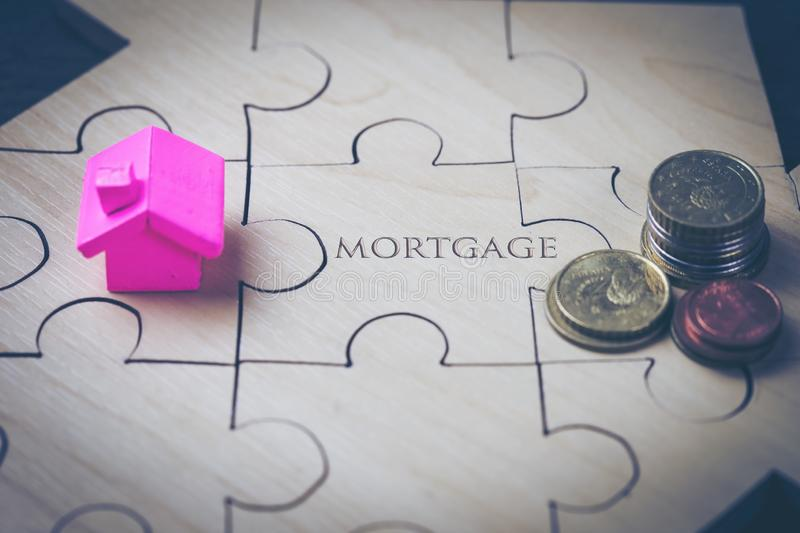 The house and coins are placed on a piece of puzzles with last piece with text mortgage. royalty free stock photos
