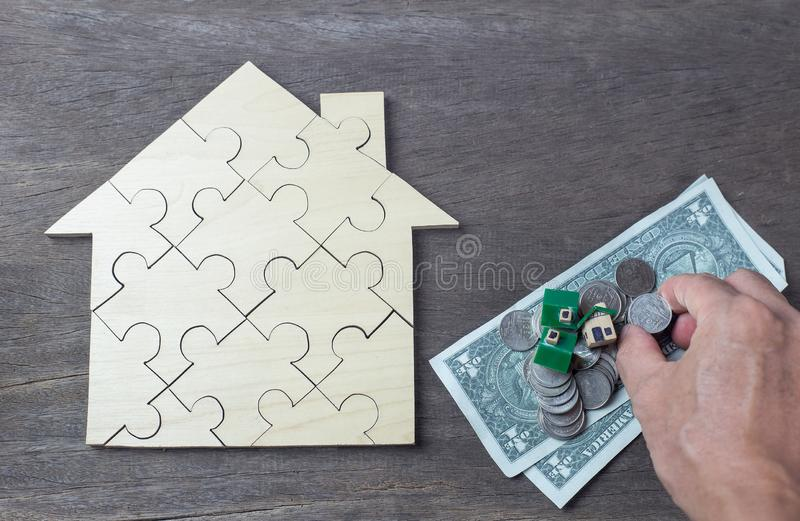The house and coins are placed on a piece of puzzles with last piece with text mortgage. royalty free stock images