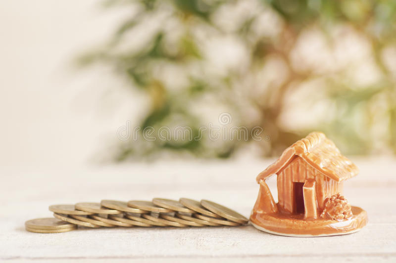House and coins stacked. On wood background, concept in growth, sell, buy, save and invest in business of home stock photos