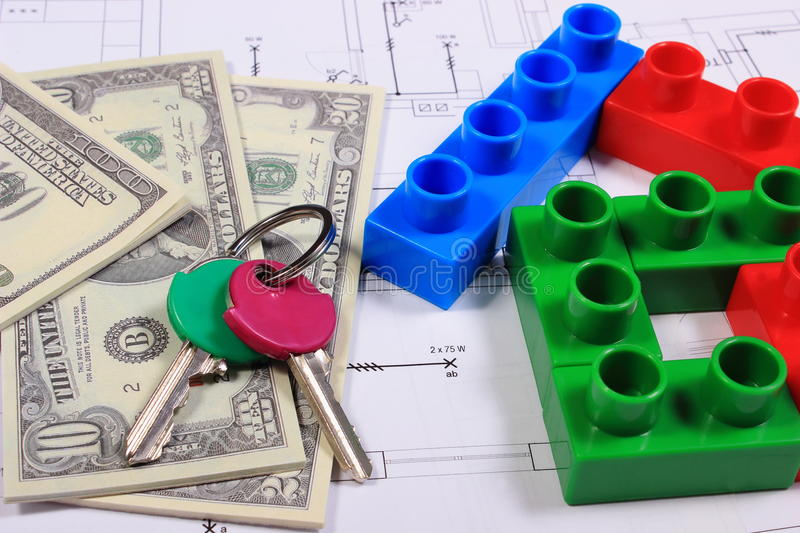House of colorful building blocks, keys and banknotes on drawing. House shape of colorful building blocks, home keys and banknotes on construction drawing of royalty free stock photos