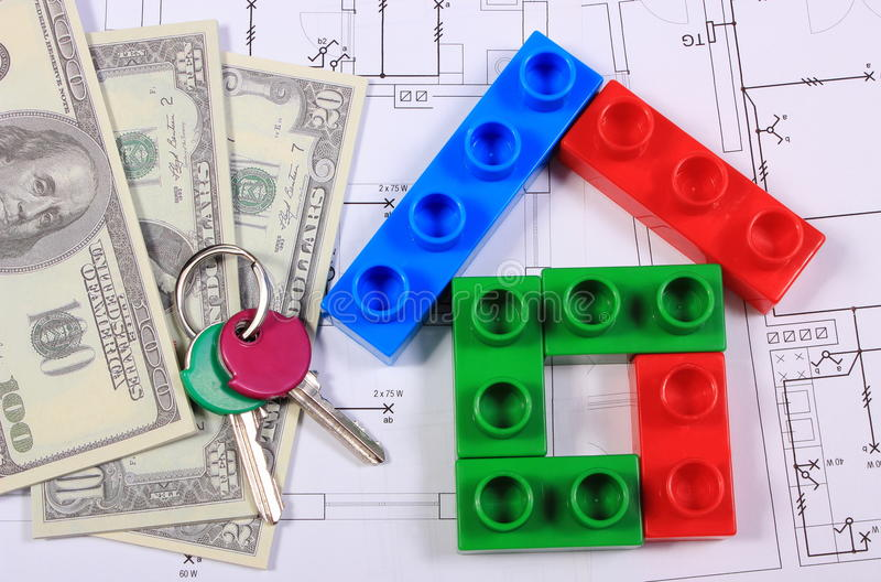 House of colorful building blocks, keys and banknotes on drawing. House shape of colorful building blocks, home keys and banknotes on construction drawing of stock photography