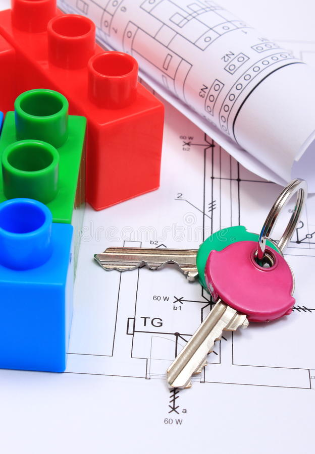 House of colorful building blocks, keys and drawings. House of colorful building blocks, home keys and electrical diagrams on construction drawing of house stock photography