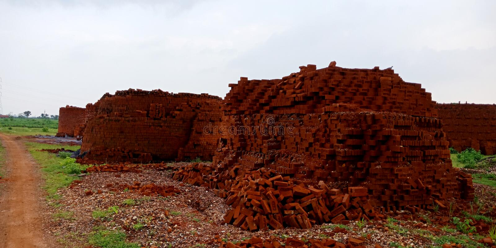 house construction material brick manufacturing plant isolated on green field in India stock photos